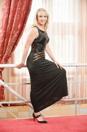 Beautiful smiling mature woman in black evening dress stands to utmost about metal handrail. photo