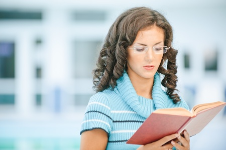 Beautiful dark-haired woman in blue sweater and glasses reads interesting red book against spacious hall. photo