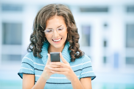 Beautiful smiling dark-haired woman in dark blue sweater and glasses on mobile phone against spacious light hall. photo