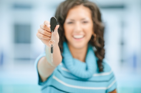 Young beautiful laughing woman in blue sweater stretches car key photo