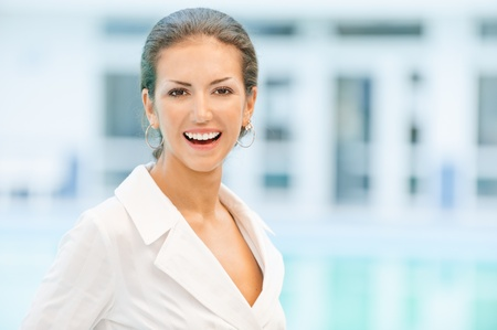 chearful: Young beautiful laughing business woman against magnificent office.