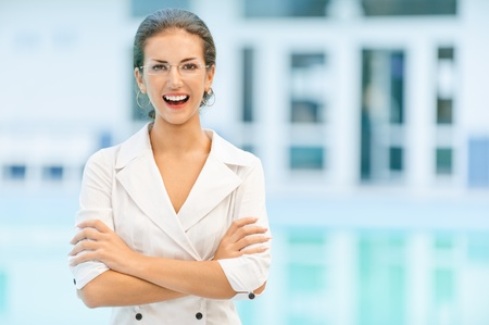 Young beautiful laughing business woman in glasses and with crossed hands against magnificent office. photo