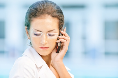 Young beautiful sad business woman in glasses talks by mobile phone and looks downwards against magnificent office. photo