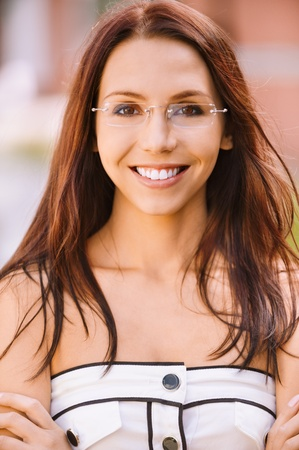 Portrait beautiful smiling young woman in white clothes and glasses with crossed hands. photo