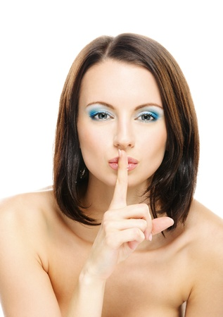 Young beautiful dark-haired woman with bared shoulders puts forefinger to lips as a sign of silence, isolated on white background. photo