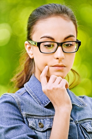 reflects: Portrait young beautiful serious dark-haired woman in glasses with dark frame which thoughtfully reflects, on green summer background.
