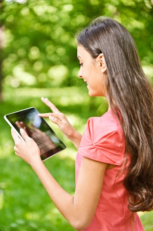 touch screen computer: Young charming dark-haired woman works on tablet computer in green summer city park., Stock Photo