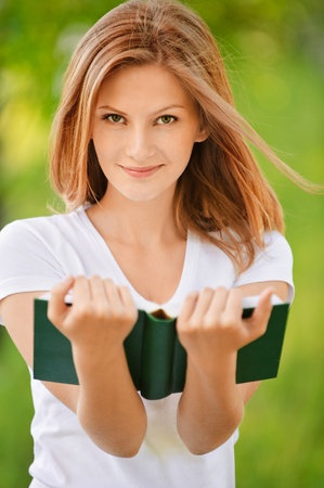 Portrait of nice young smiling woman with book on green background of city park. Stock Photo - 9771214