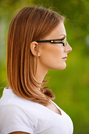 Beautiful young smiling woman in white blouse and glasses, profile close up, on green background of city park.