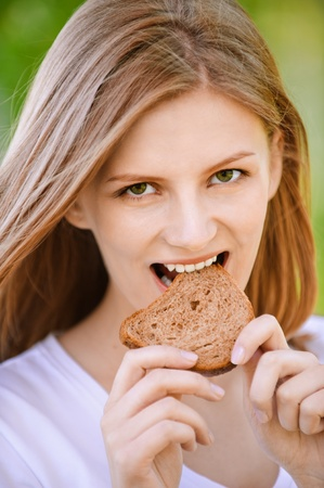 stale: Young beautiful woman bites piece of stale bread, on green background of summer city park.