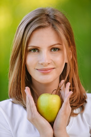 Young fine woman holds apple and smiles, on green background of summer city park. photo