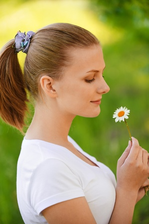 Young charming woman holds small camomile and lovely smiles, on green background of summer city park. photo