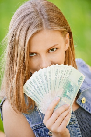 Young artful woman closes face fan from Russian roubles, on green background of summer city park. photo