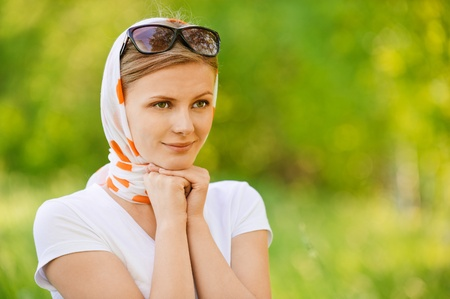 sunshades: Young attractive woman in headscarf with sunshades, on green background of summer city park. Stock Photo