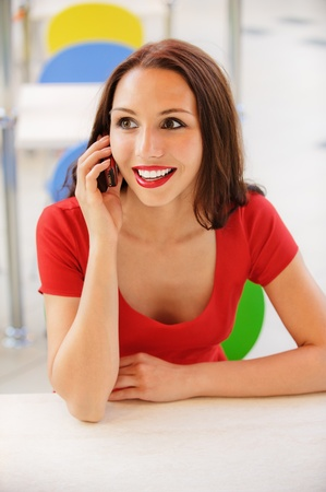 expects: Beautiful young woman in red dress sits at little table in cafe and order expects.