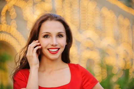 Young beautiful smiling woman in red dress talks by mobile phone against evening illumination. photo