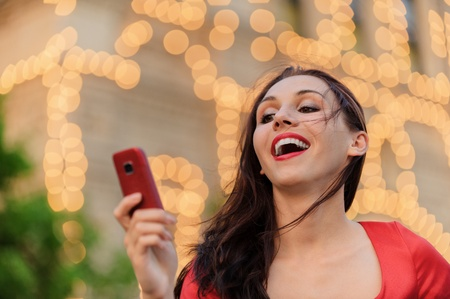 Young beautiful smiling woman in red dress reads text message on mobile phone against evening illumination. photo