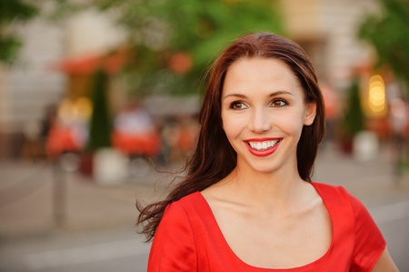 vespers: Young beautiful smiling woman in red dress against city vespers.
