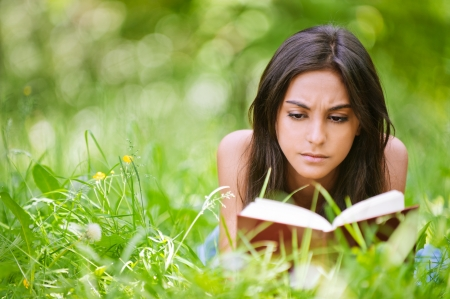 Young nice attentive woman lies on green grass and reads book against city park. photo
