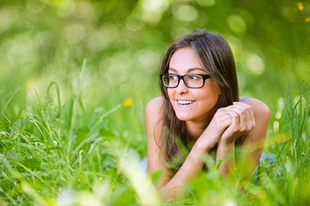 Young charming smiling dark-haired woman in glasses with black frame lies on green grass in summer city park. photo