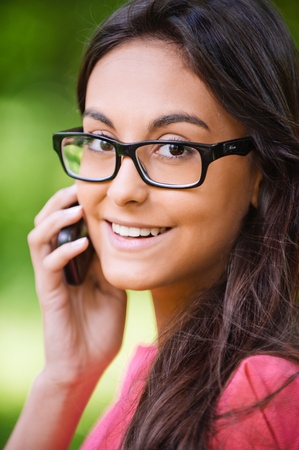 Young beautiful dark-haired woman in glasses black are right talks on cellular telephone and smiles, against green summer garden. Stock Photo - 9863598