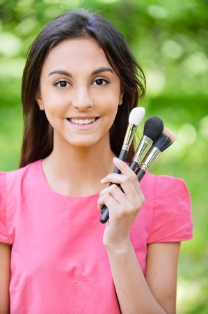Young beautiful smiling woman in red dress with set make-up of brushes against green summer garden. photo