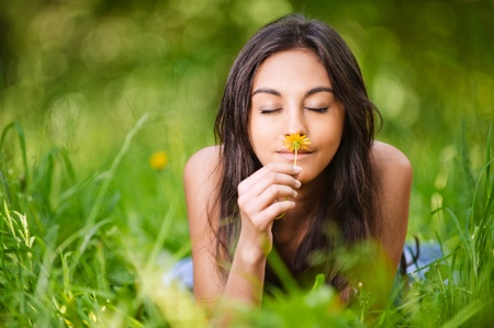 odor: portrait of beautiful young long-haired woman lying in park and smelling flowers Stock Photo