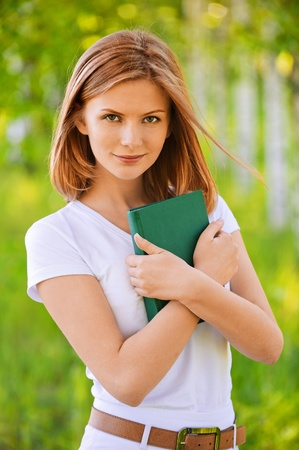 portrait of beautiful young blond woman holding book in summer green park photo