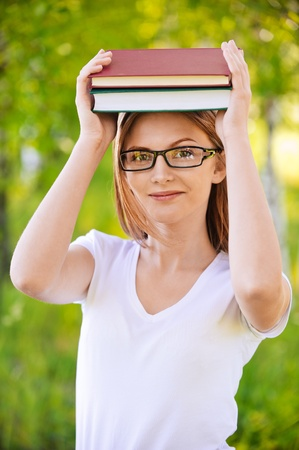 portrait of beautiful young blond woman in glasses holding books at summer green park Stock Photo - 9980655