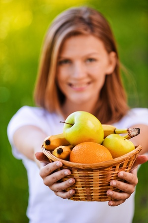 portrait of young beautiful blond smiling woman holding a basket with fresh juicy fruits in summer green park photo