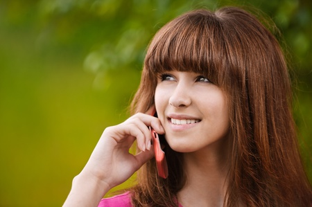 Portrait of young beautiful smiling dark-haired woman talking on telephone at summer green park. Stock Photo - 9980669