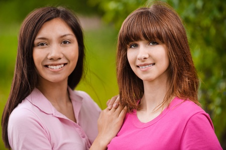 Two young smiling brunette bright clothed women standing in park. Stock Photo - 9980720