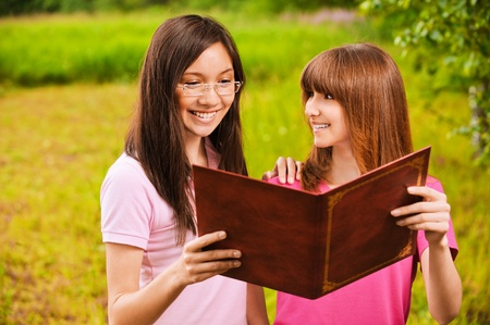 Two beautiful young bright clothed women read book together at summer green park. Stock Photo - 9980730