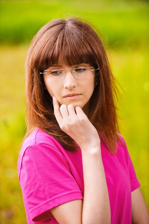 Portrait of young pensive woman in pink blouse wearing eyeglasses standing at park and looking somewhere. Stock Photo - 9980718