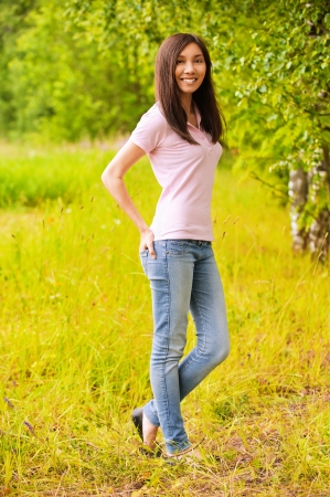 Full-length portrait of young beautiful smiling casually clothed woman at summer green park. photo