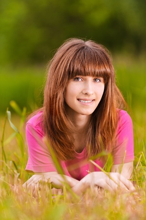 Portrait of young beautiful smiling woman lying on green meadow. Stock Photo - 9980723