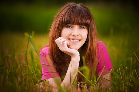 Portrait of young beautiful smiling woman lying on grass at summer park and propping up her face. Stock Photo - 9980706