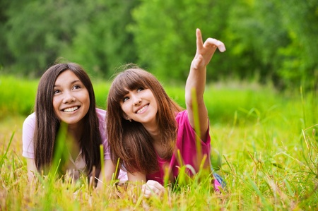 Two young joyful pretty women stare to the sky, one of them points at something. Stock Photo - 9980695
