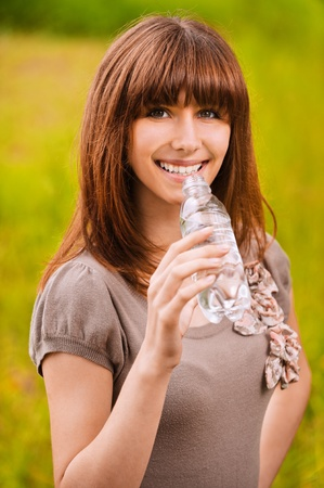 Portrait of young smiling woman drinking water at summer green park. Stock Photo - 9980728