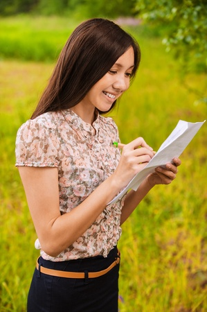 pencil skirt: Portrait of young smiling woman whriting something on sheet of paper.