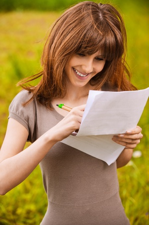 Young happy smiling woman writes something on sheet of paper. Stock Photo - 9980725