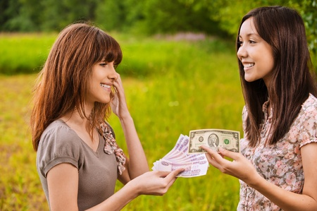 concluding: Two young women concluding a bargain, exchanging currency at summer green park.