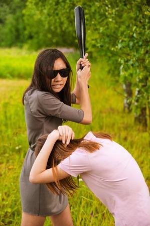 celos: Joven mujer agresiva morena en gafas de sol golpea a otro con un bate en el verano de parque verde.
