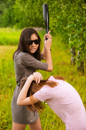 jealousy: Young aggressive brunette woman in sunglasses hits another with bat at summer green park.