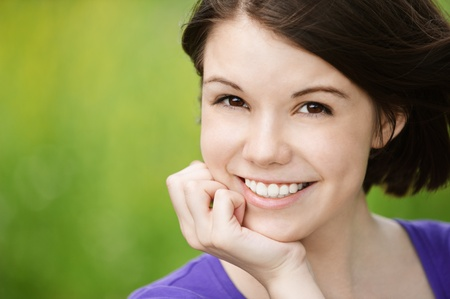 chuckle: Close-up portrait of young beautiful smiling woman propping up her face in front of summer green park.