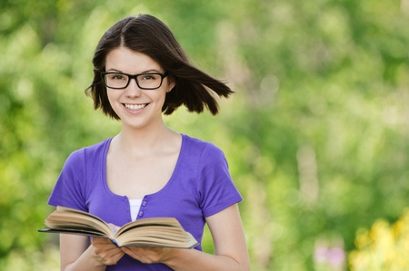 Portrait of young attractive smiling woman wearing violet blouse and eyeglasses standing at summer green park. photo