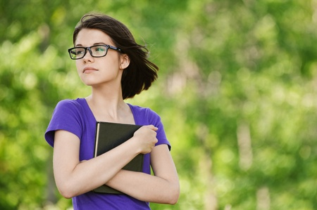 Portrait of young pretty woman wearing glasses and violet blouse holding book and staring somewhere at summer green park. photo