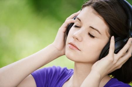 mujer pensativa: Retrato de primer plano de joven pensativa escuchando m�sica en el Parque de verano verde.