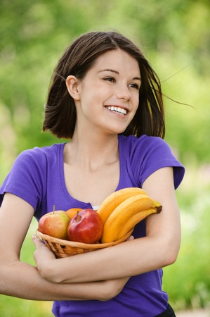 Portrait of young beautiful attractive smiling woman holding basket full of fruits at summer green park. Stock Photo - 9980777