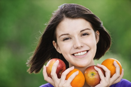 Portrait of young beautiful cheerful happy brunette woman holding fruits. photo